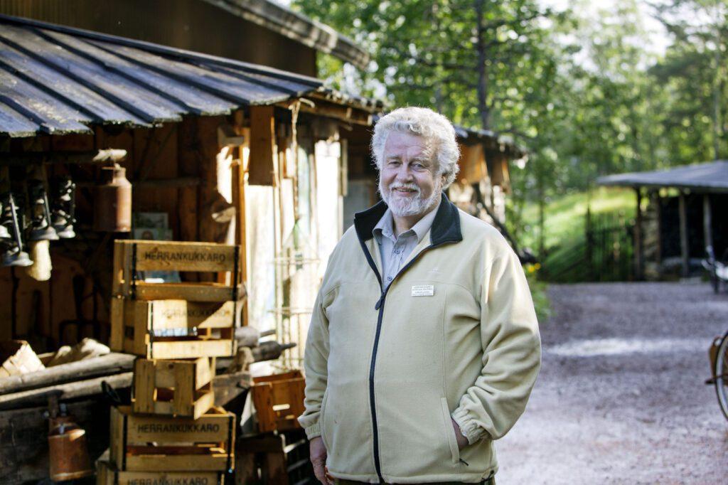 Herrankukkaron isäntä Pentti-Oskari Kangas hymyilee kameralle Herrankukkaron rakennusten vieressä kesällä.
