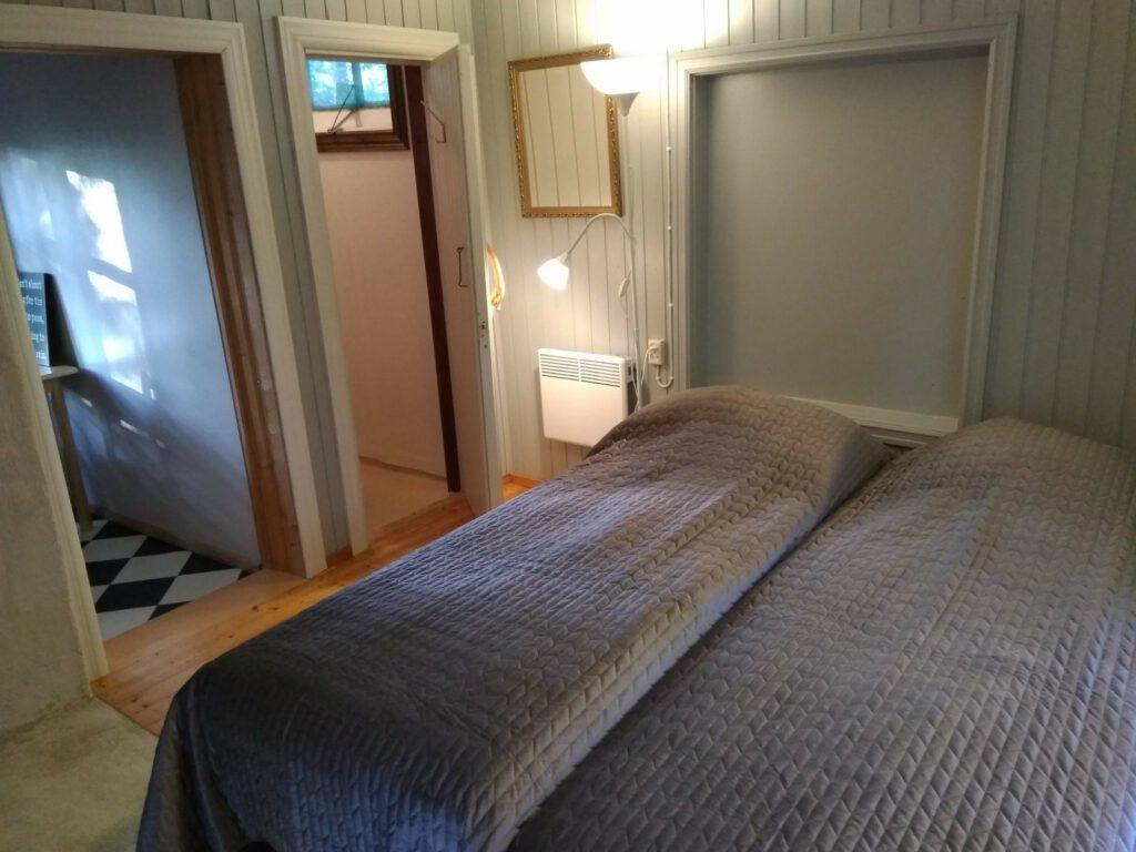 Päiväkulman makuuhuone, jonka sängyllä harmaa päiväpeitto.