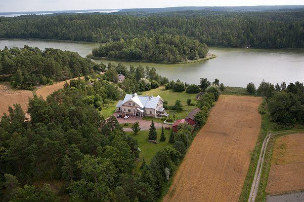 Ilmakuva vaaleankeltaisesta Päiväkulman tilan päärakennus metsien ja peltojen keskellä, lähellä meren rantaa.