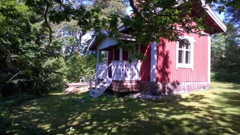 Punainen mökki puutartahan keskellä.
