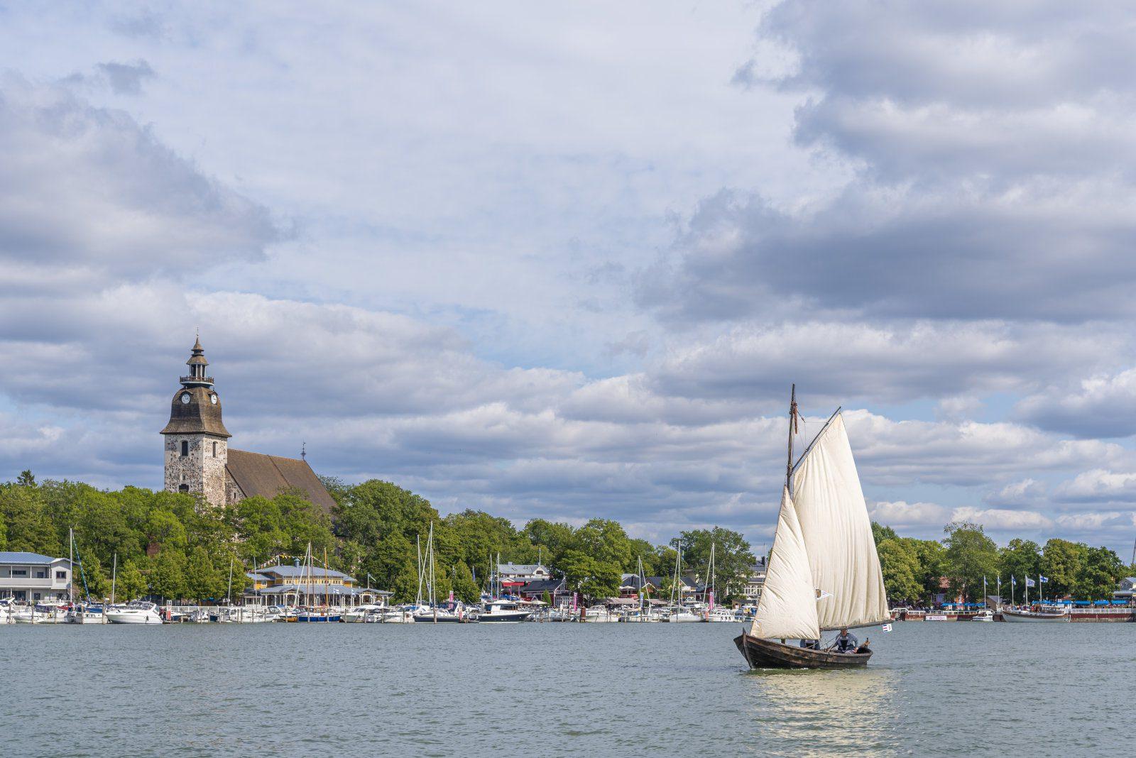 Naantalin kirkko mereltä päin, kuvan edessä perinnepurjelaiva valkoisilla purjeilla. Pilvinen taivas.