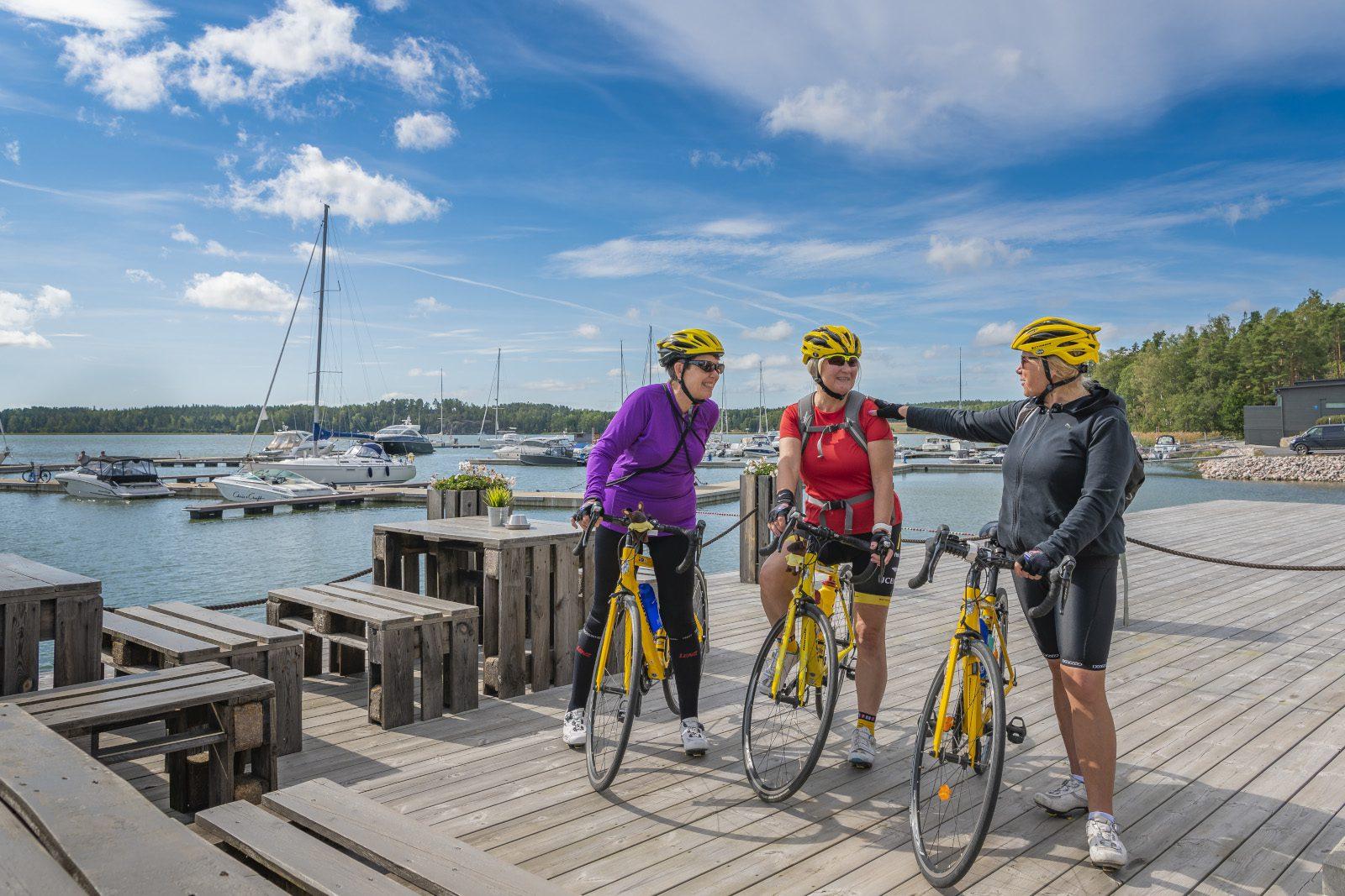 Kolme pyöräilijää rantalaiturilla. Kesäpäivä, sininen taivas, taustalla näkyy vierasvenesataman veneitä.
