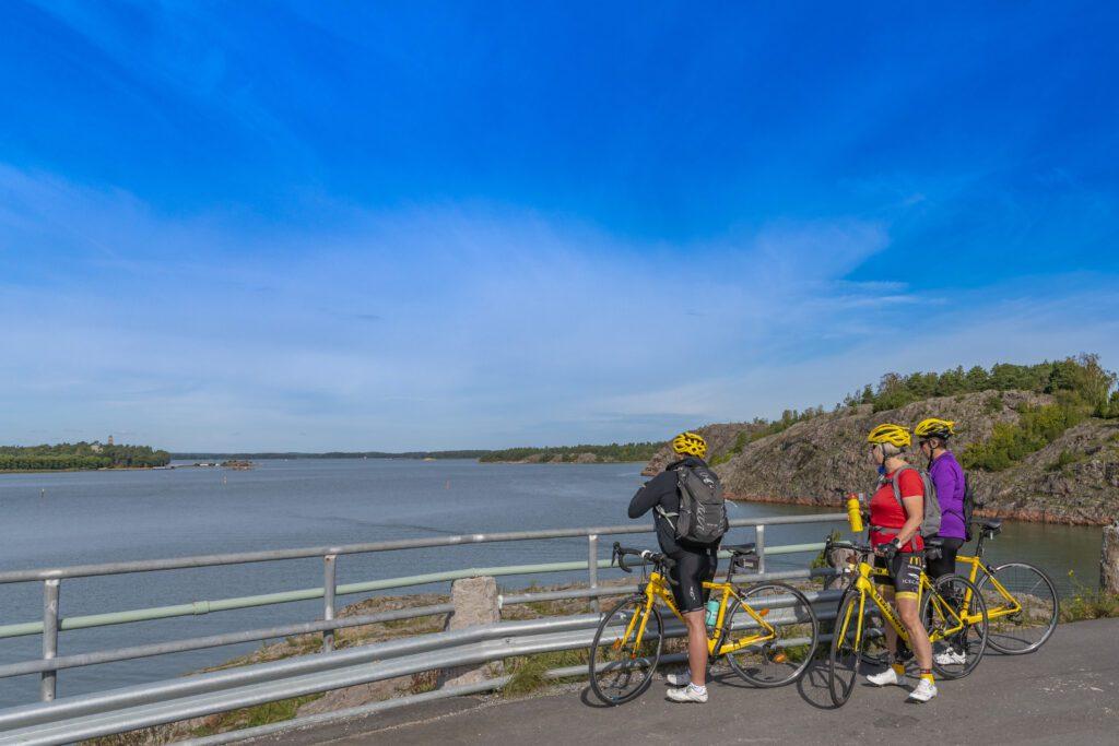 Kolme pyöräilijää katsoo merimaisemaa sillalta.