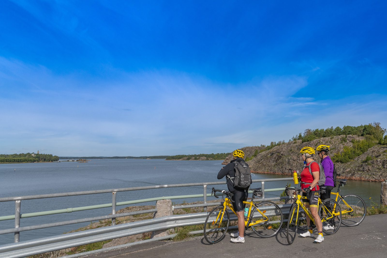 Kolme pyöräilijää katsovat merimaisemaa sillalta. Pilvetön taivas, sininen taivas ja meri, kallioita oikella ja Kultarannan linna näkyy vasemmalla.