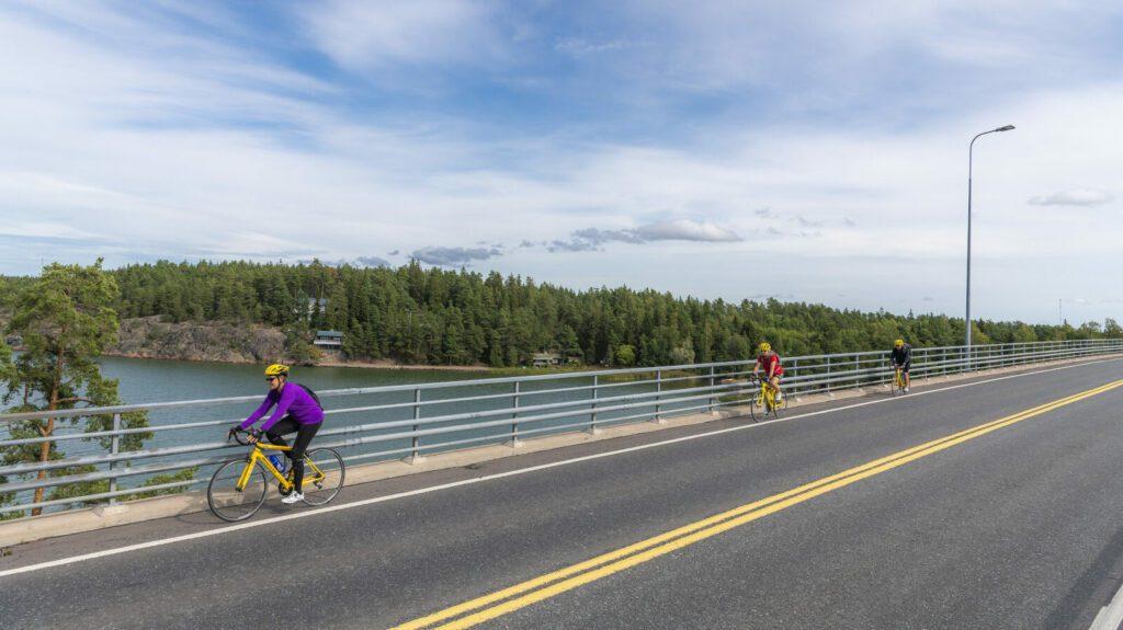 Kolme pyöräilijää pyöräilee sillan yli. Merta ja saarta näkyy sillan kaiteen takana.