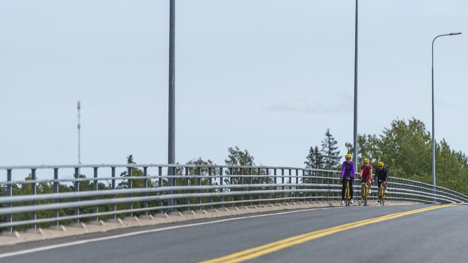 Kolme pyöräilijää pyöräilevät sillan yli, näkyy siltaa ja harmaata taivasta.