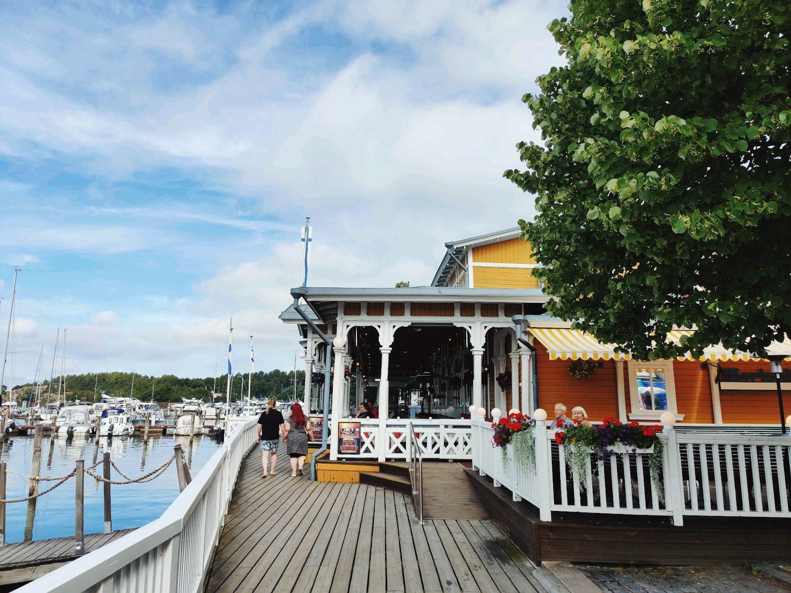 Kävelylaituri ja keltainen ravintolarakennus, valkoiset kaiteet. Sininen taivas, muutamia pilviä, puu kuvan oikeassa reunassa.