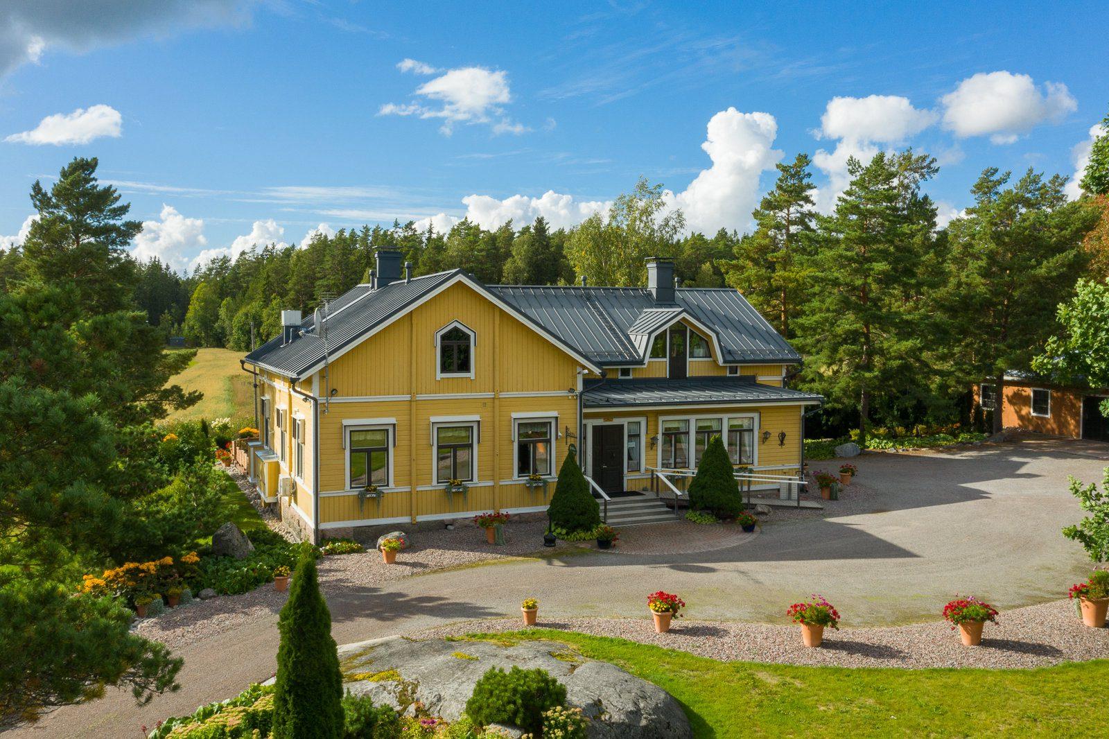 Ravintola Pohjakulman keltainen pääkuva ja piha. Kukkaruukuissa punaisia kukkia, taustalla metsää ja peltoa. Sininen taivas ja muutamia pilviä.