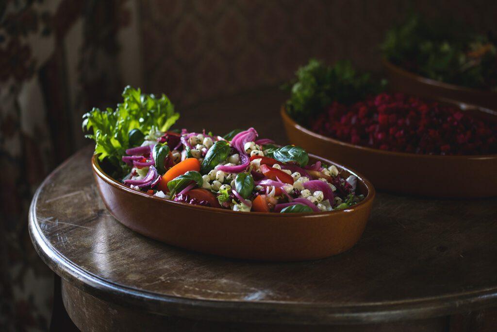 Ravintola Pohjakulman tarjoilupöydän salaattikulho, jossa punasipulia, mozzarellapalloja, tomaattia ja basilikaa.