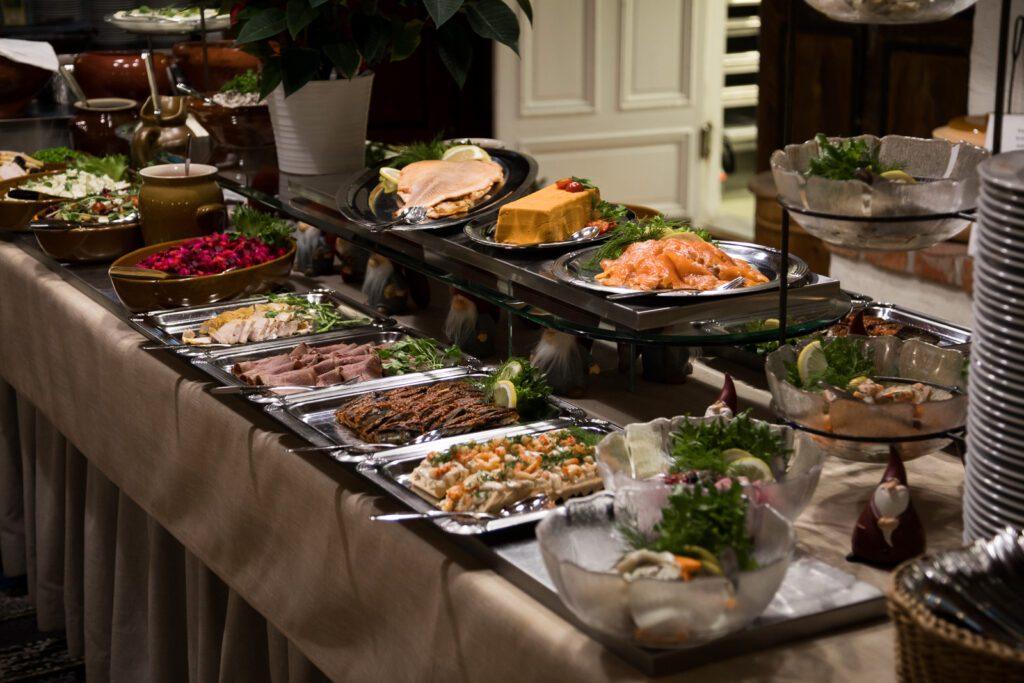 Ravintola Pohjakulman seisovan pöytä, jossa tarjoiluastioissa kylmiä leikkeleitä, lohta, ja rosollia.