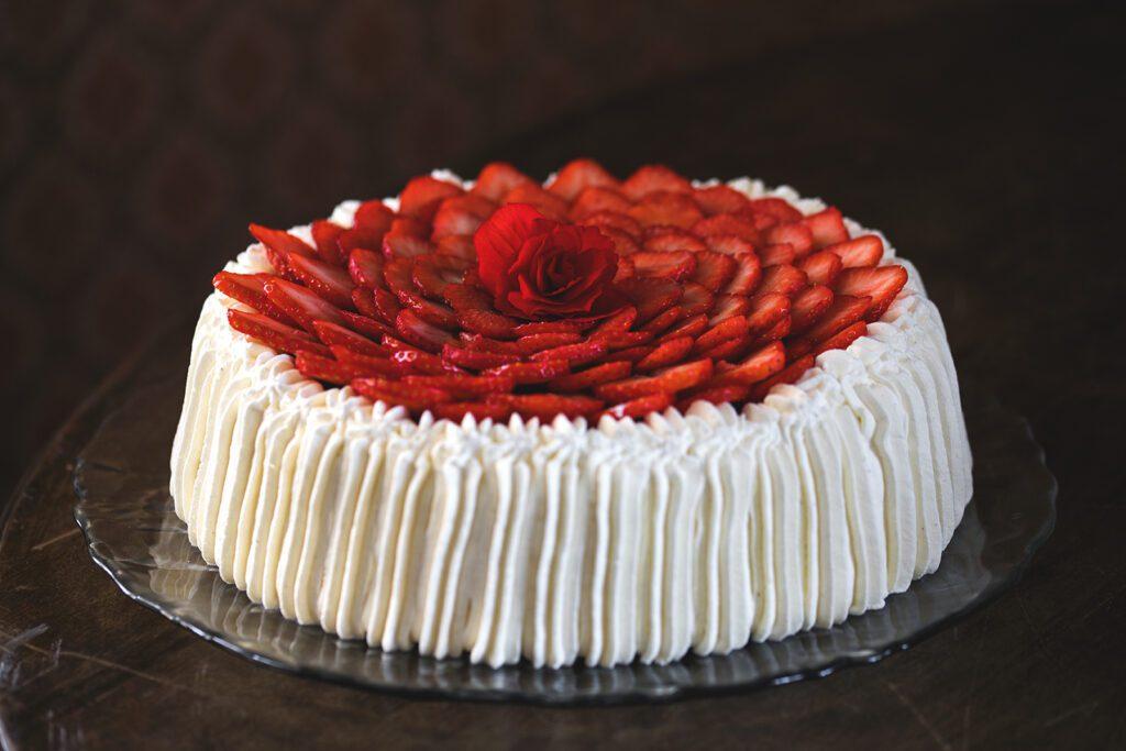 Ravintola Pohjakulman täytekakku, valkoista kermaa reunoilla ja kakun päällä viipaloituja mansikoita ja punainen ruusu.
