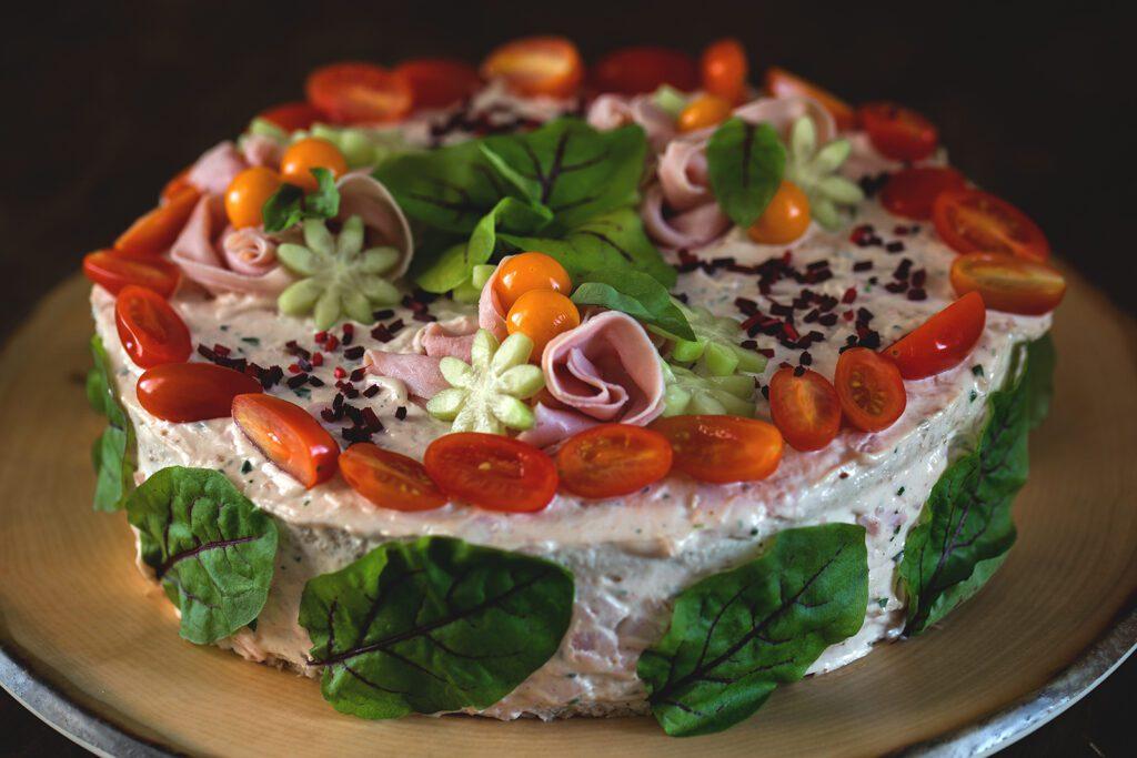 Ravintola Pohjakulman pyöreä voileipäkakku, joka on koristeltu kirsikkatomaatteja, kurkkua, kinkkua ja salaatinlehtiä.