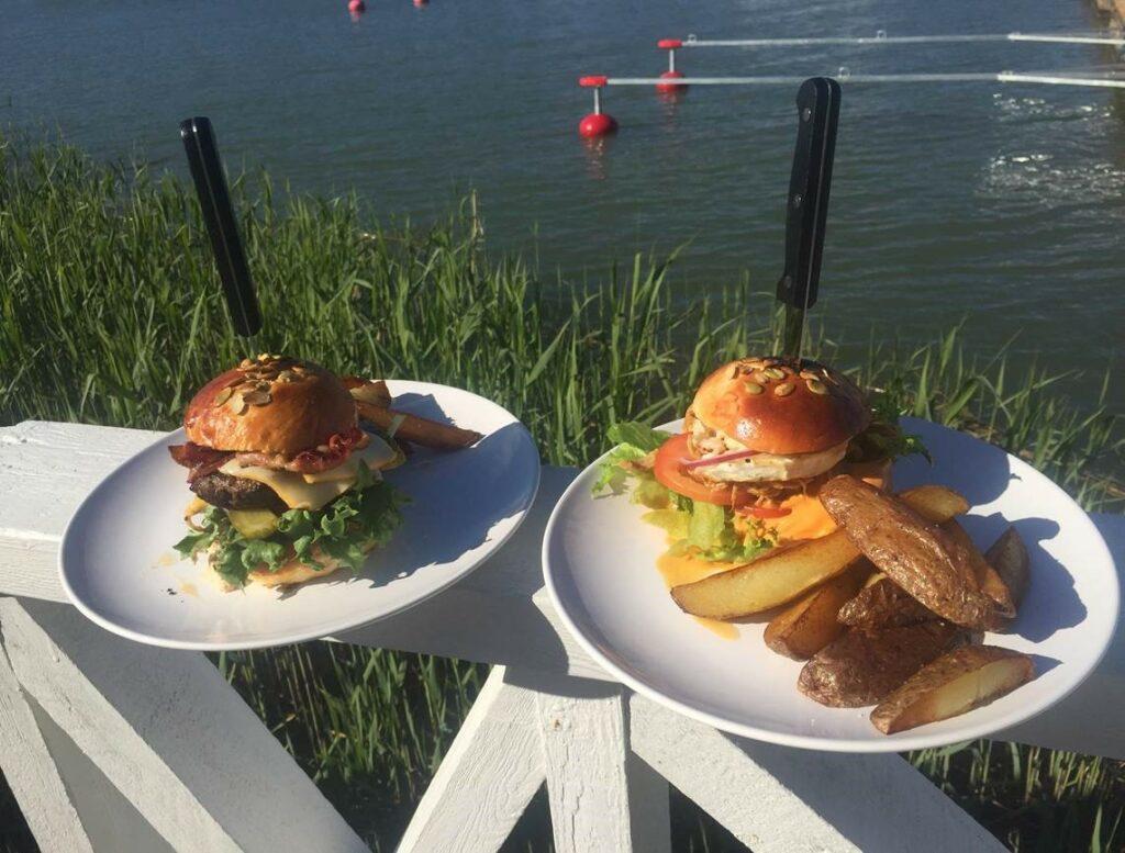 Kaksi Merimaskun Rantamakasiinin burgeriannosta lautasilla laiturin kaiteen päällä.