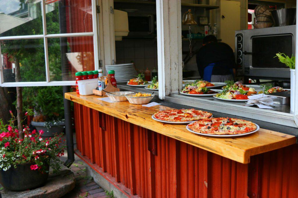 Punaisen keittiörakennuksen ikkunan karmitaso, jossa kaksi pitsaa ja salaattiannoksia odottamassa tarjoilijaa.