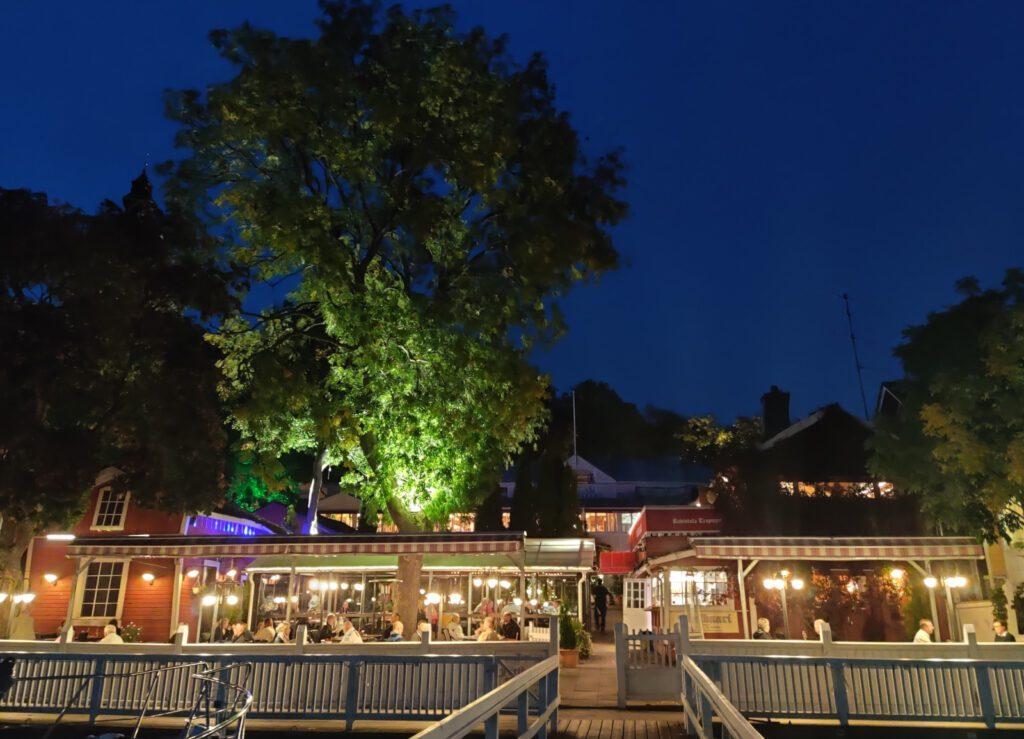 Rantaterassi, laiturit yöllä, valo valaisee isoa puuta ja terassi on valaistu lyhdyin.