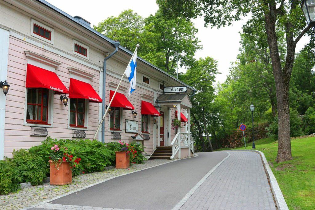 Vaaleanpunainen ravintolarakennus ja kivetty katu puiston varrella. Suomenlippu talon kyljessä, ikkunoissa punaiset markiisit, joissa lukee Ravintola Trappi.