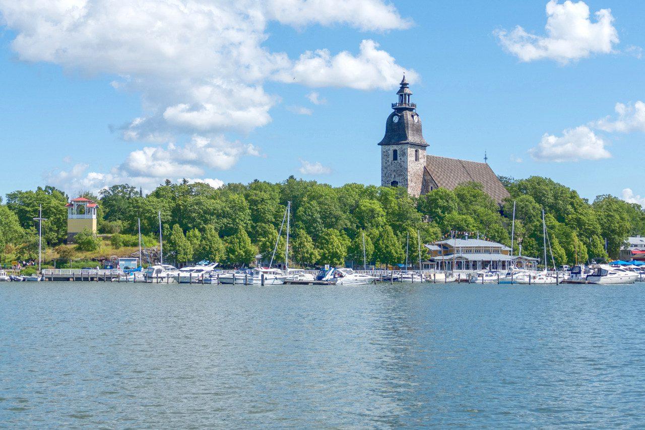 Naantalin kirkko ja Naantalin ranta, vierasvenesataman veneitä ja purjeveinitä sekä keltainen näkötorni mereltä päin kuvattuna. Aurinkoinen kesä päivä, muutamia pilviä taivaalla.