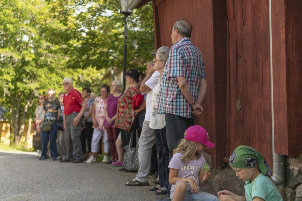 Opastetulle vanhan kaupungin kierrokselle osallistuvia kuuntelee opasta punaista puutalonseinää vasten..