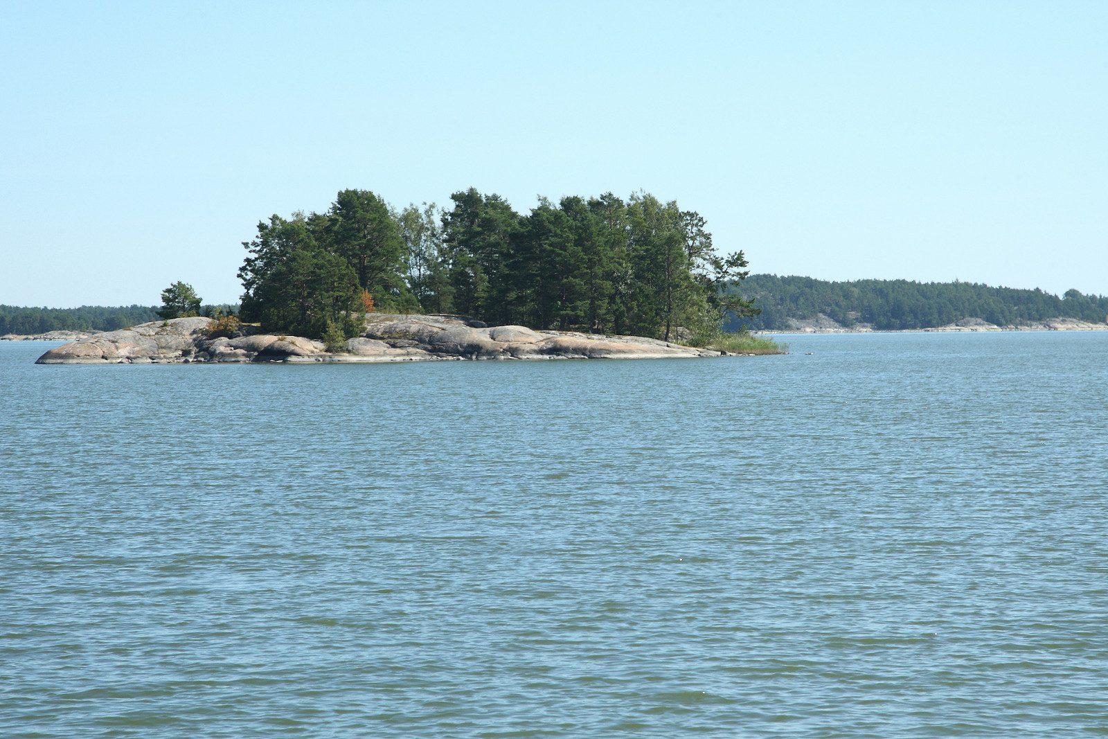 Kesäinen meri, kalliosaari, jolla muutamia puita, sininen taivas.
