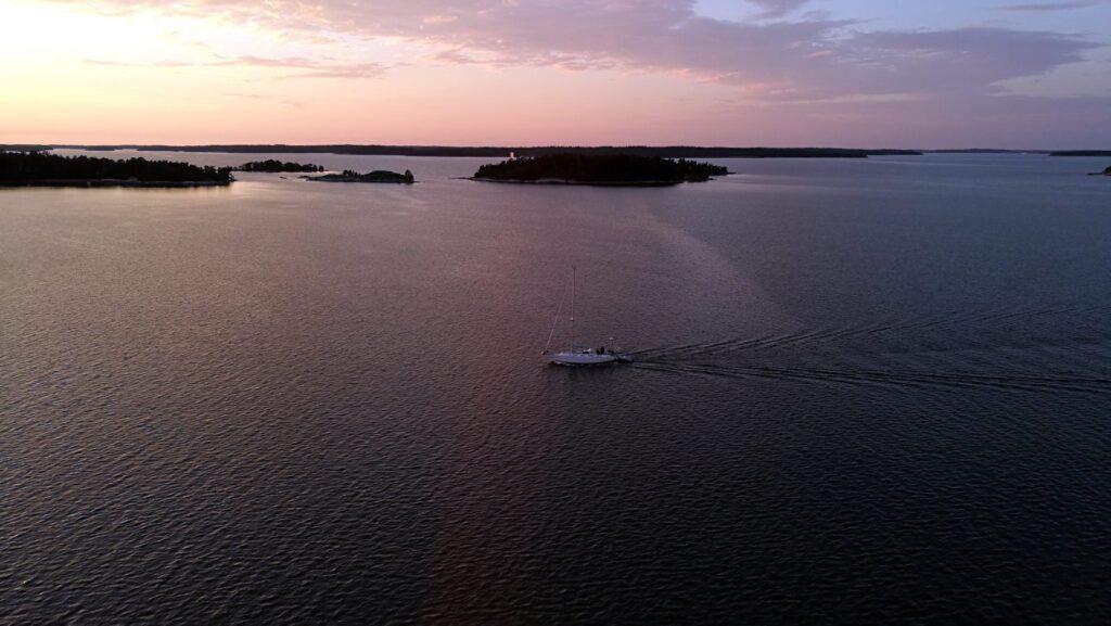 Aava meren ulappa iltaruskon aikaan, valkoinen purjevene..