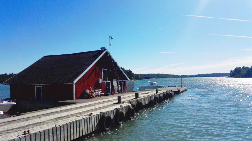 Punainen venevaja ja harmaa laituri. Merta ympärillä, pilvetön sininen taivas.