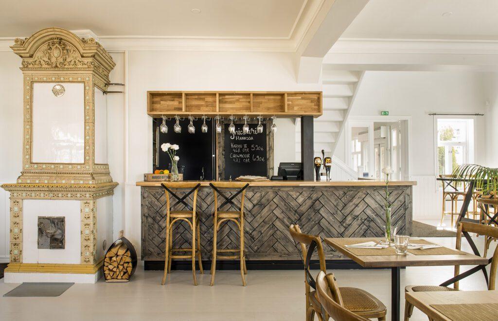 Snickari-ravintolan baari, jonka edessä jakkaroita ja vieressä koristeellinen valkoinen ja kultainen kaakeliuuni.