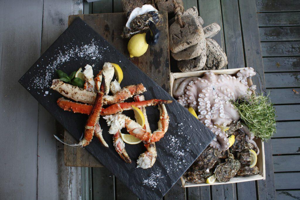 Snickari-ravintolan annoskuva, jossa tarjoiluastioiden päällä mereneläviä kuten mustekalaa, hummerin jalkoja ja simpukoita.
