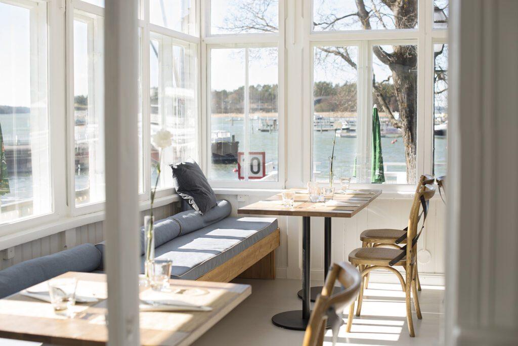 Snickari-ravintolan sisäterassin pöydät ja penkki, ikkunoista näkyy meri.
