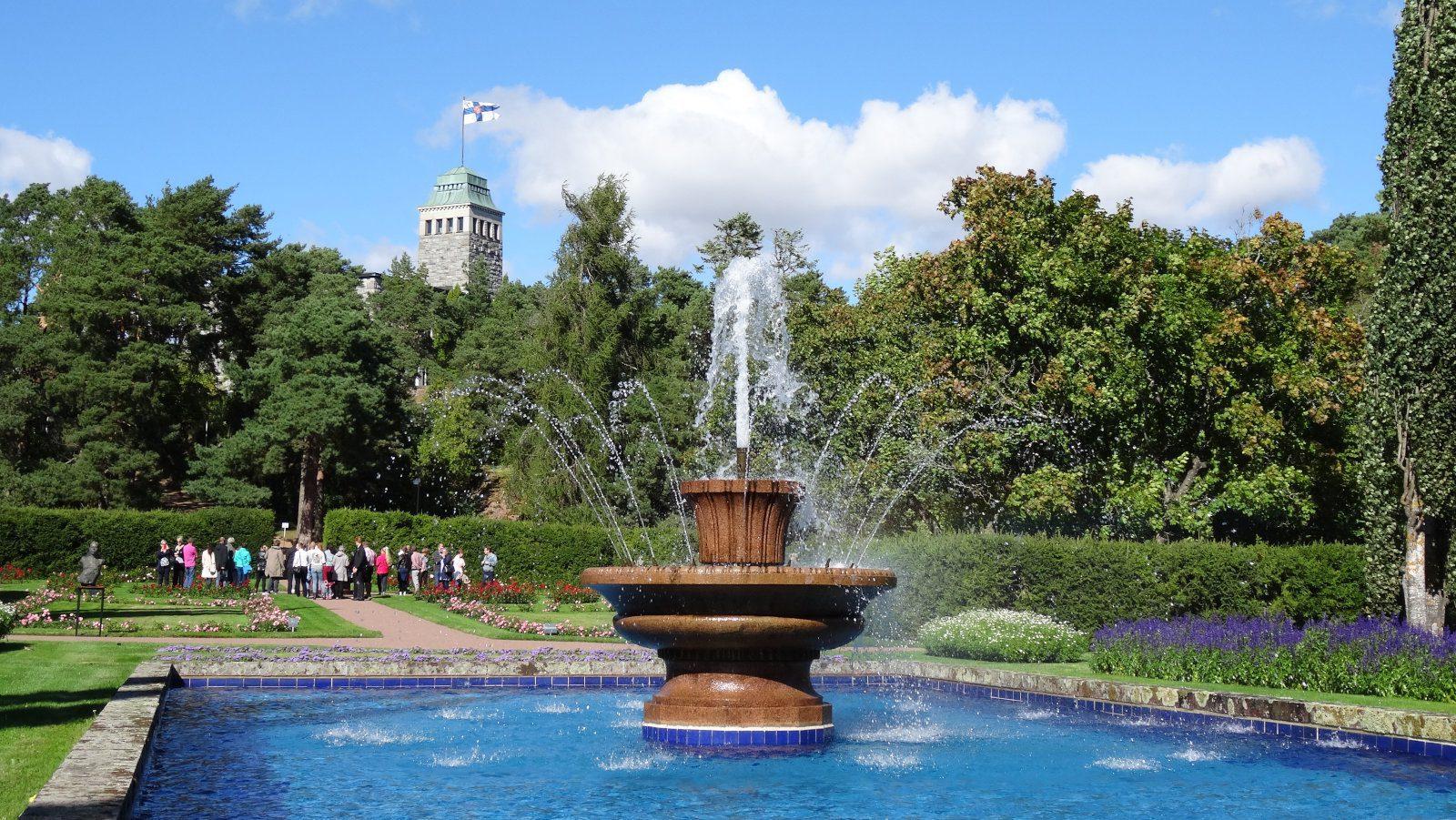 Kultarannan puutarhan iso suihkulähde ja sininen allas, vesi suihkuaa korkealle. Takana Kultarannan kivilinna, jonka tornissa liehuu Suomen lippu.