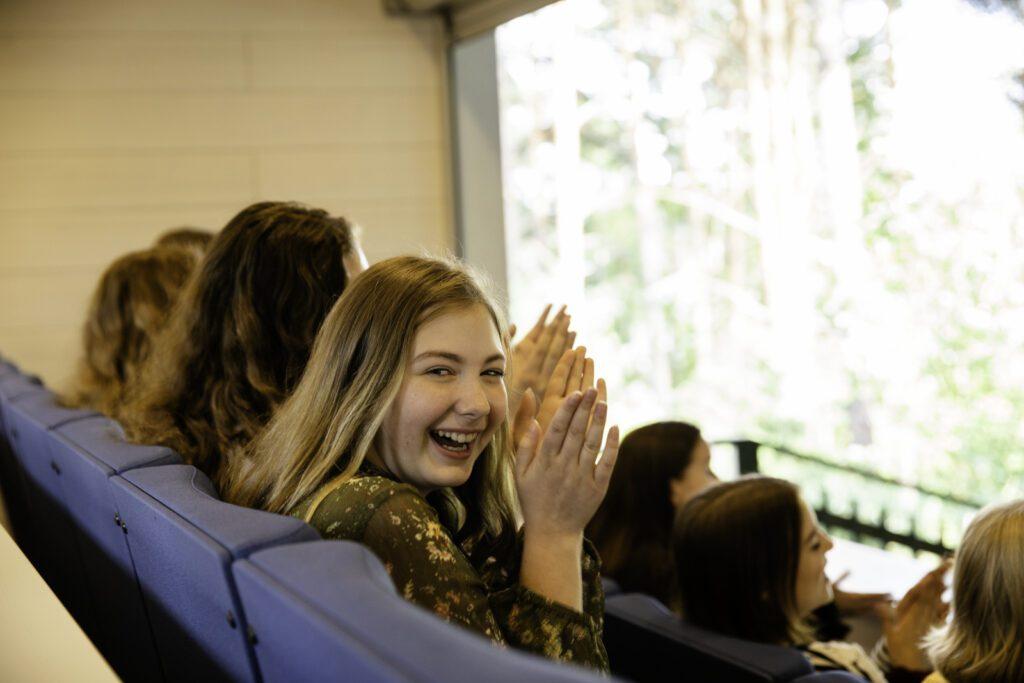 Emma Teatterin aition penkkirivi, jossa istuu yleisöä. Taputtava tyttö katsoo olan yli ja hymyilee kameralle.