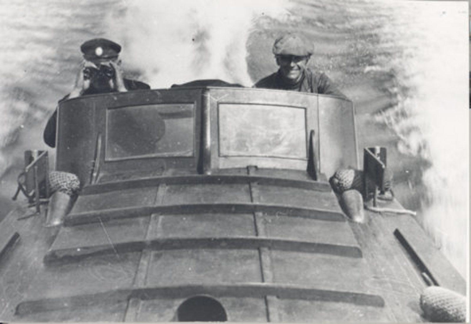 Mustavalkoinen valokuva kahdesta miehestä, jotka ajavat venettä kovaa kyytiä.