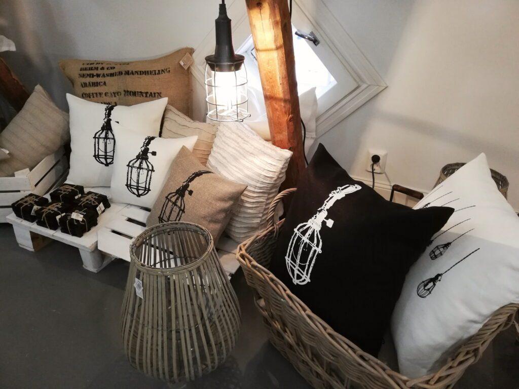 Tarja Ritari Designin valkoisia, ruskeita ja mustia pellavatyynyjä korissa ja hyllyllä.