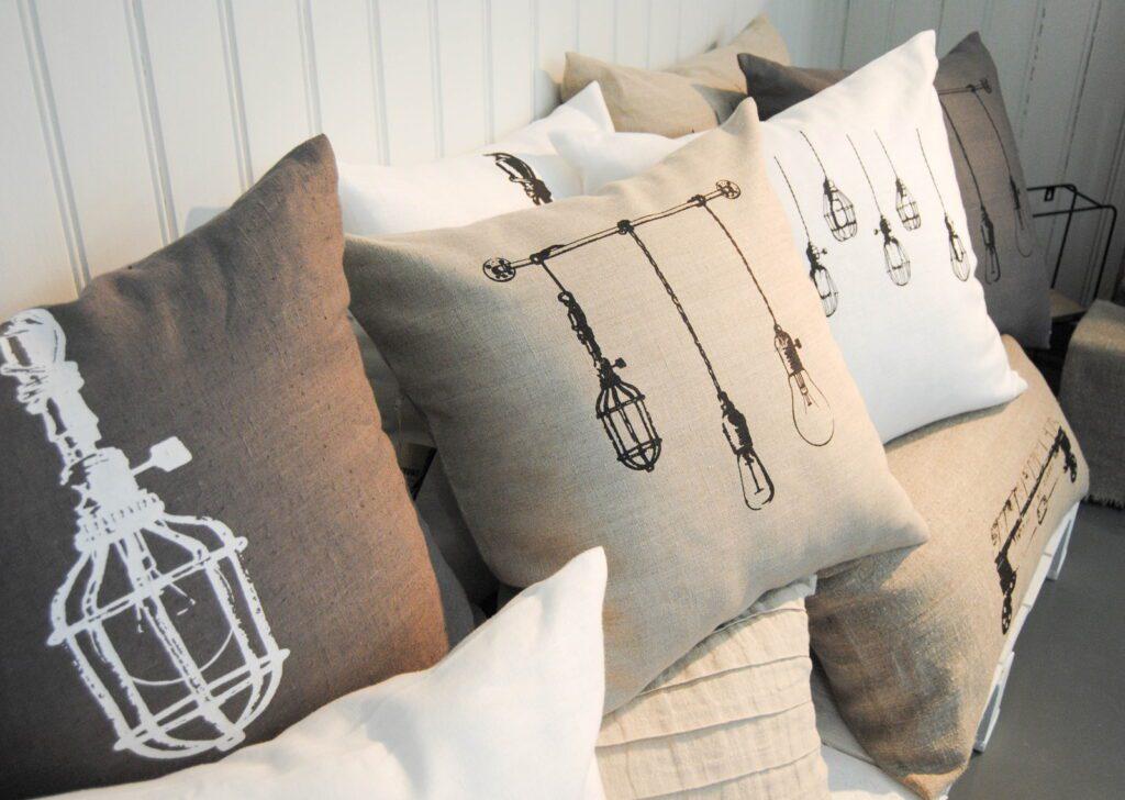 Tarja Ritari Designin kolme pellavatyynyä. Painokuviona lamppu harmaalla ja valkoisella kankaalla.