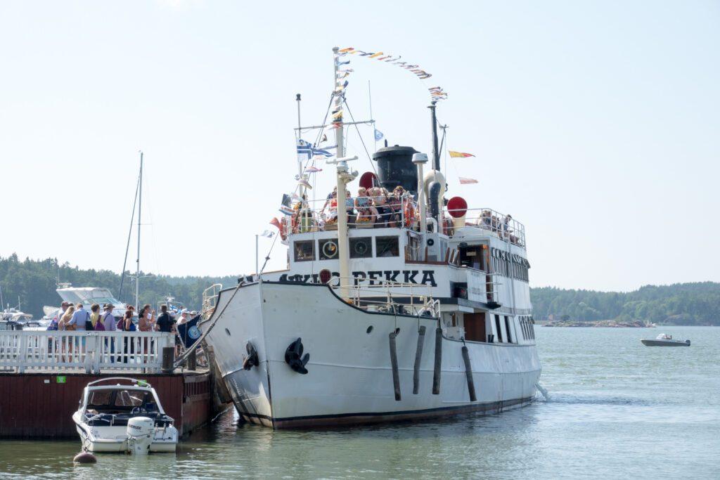 Valkoinen höyrylaiva Ukkopekka Naantalin laiturissa, lippuja liehuu kannella ja ihmisiä on sekä laivalla että laiturilla.