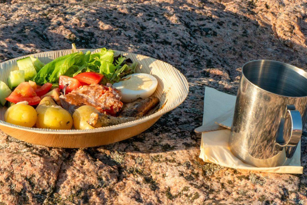 Ukkopekan Loistokarin saaren kalliolla ruokalautanen ja peltinen muki.