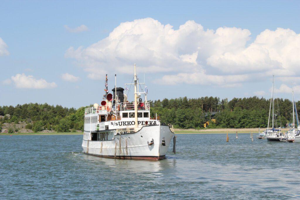 Valkoinen höyrylaiva Ukkopekka lipuu Naantalin satamaan, taustalla saari ja poutapilvinen taivas.