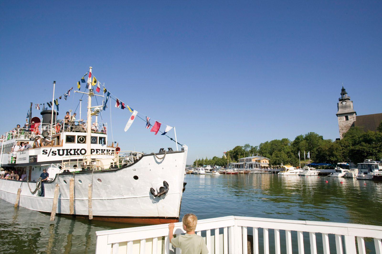 Höyrylaiva Ukkopekka, valkoinen keula ja värikkäitä lippuja kannella, saapuu Naantalin laituriin. Taustalla merta ja Naantalin kirkon torni.