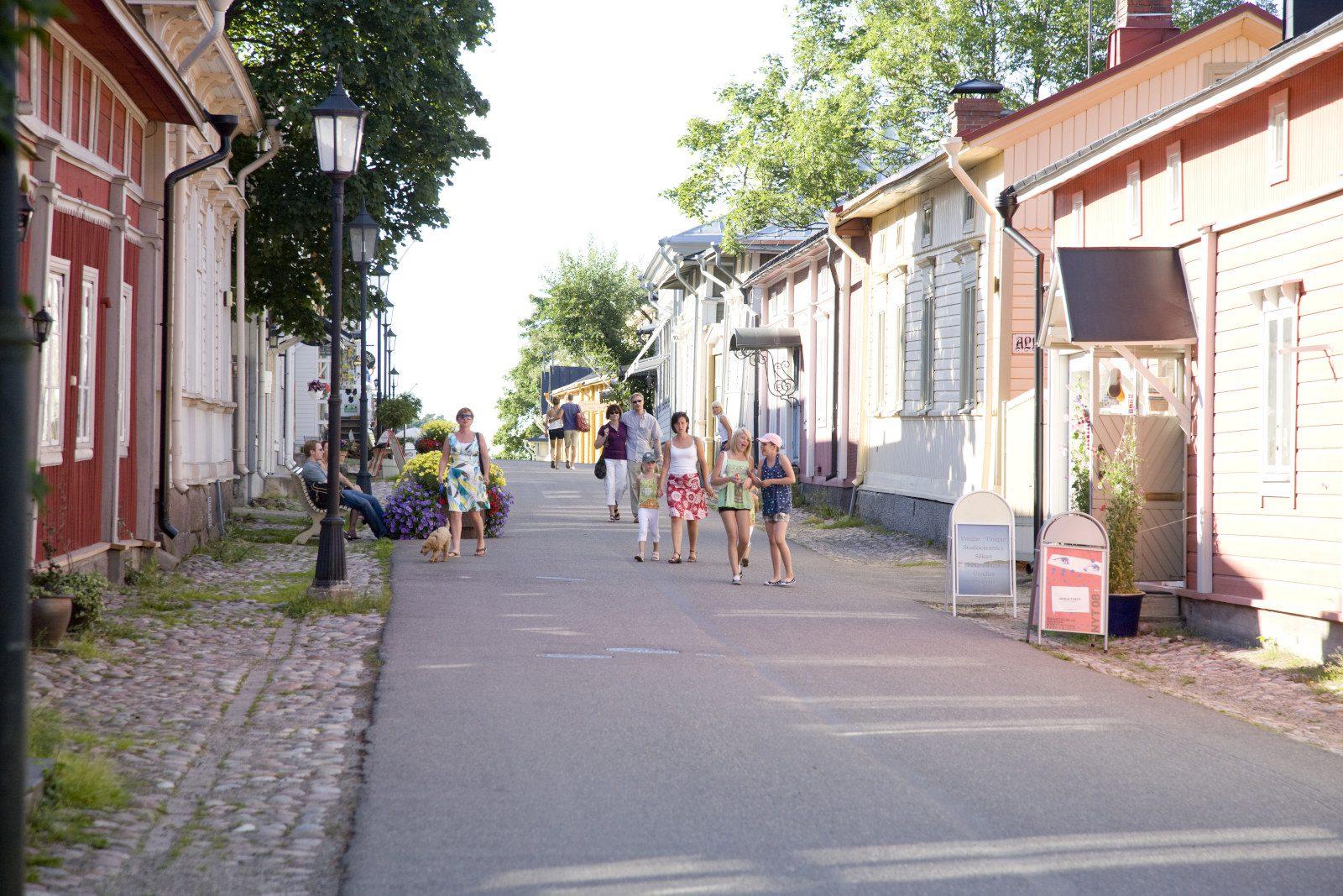 Naantalin Mannerheiminkatu kesällä, ihmisiä kävelee asfalttia pitkin, puutalot reunustavat katua, puita ja poutaista taivasta taustalla.
