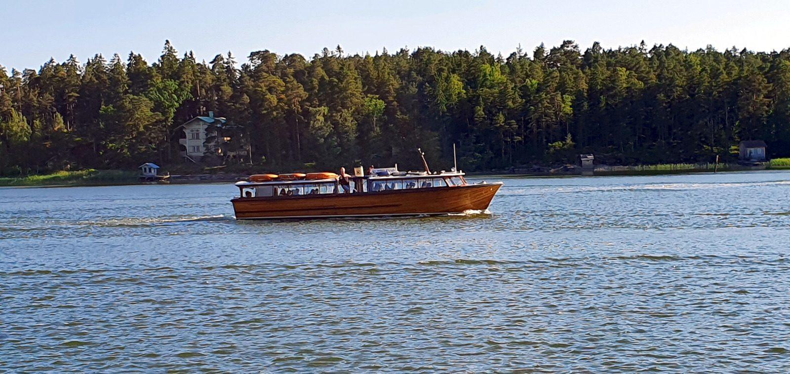 Vesibussi Kuha iltaristeilee merellä, taustalla näkyy metsäistä rantaa.