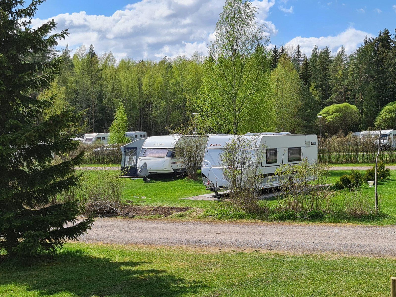 Villan tilan asuntoautoalue, kolme valkoista autoa parkissa nurmikolla.