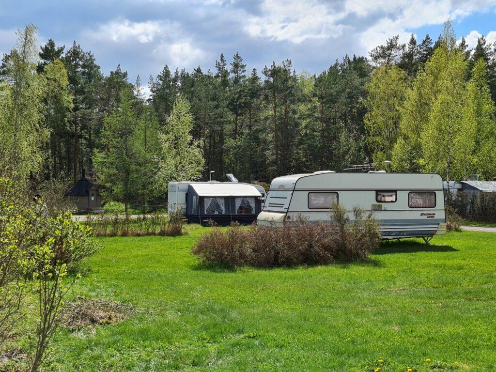 Villan tilan leirintäalue, kaksi valkoista asuntoautoa parkissa nurmikolla.