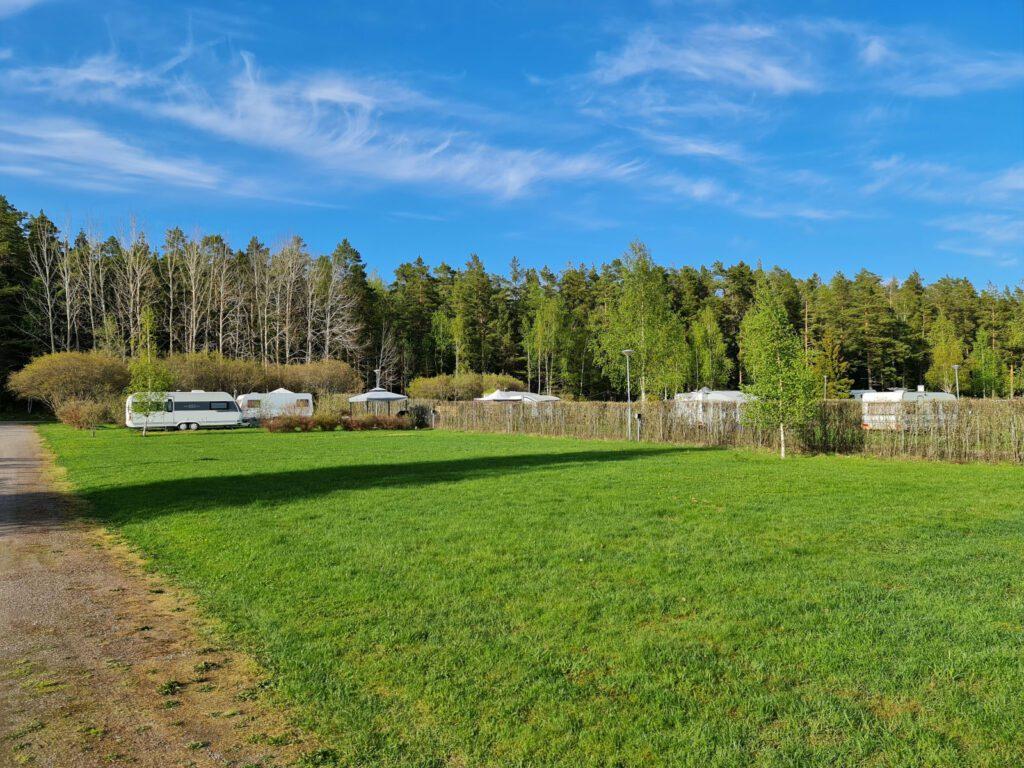 Villan tilan leirintäalue, nurmikko ja asuntoautoja.
