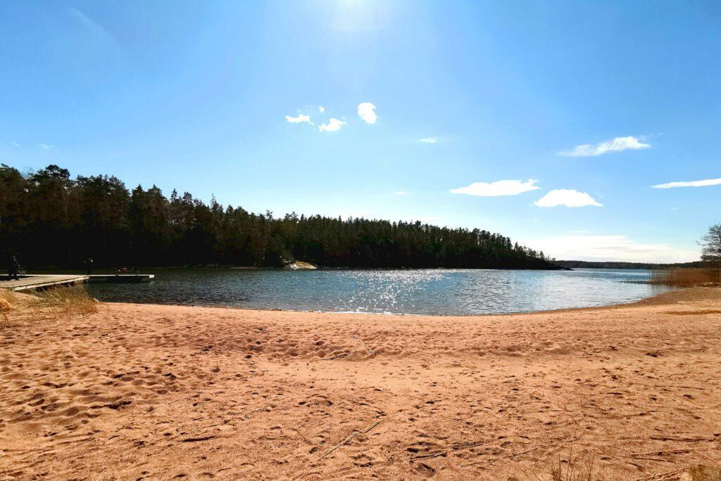 Kaareva hiekkaranta, merenlahti, jota reunustaa horisontissa puinen ranta. Sininen, pilvetön taivas.