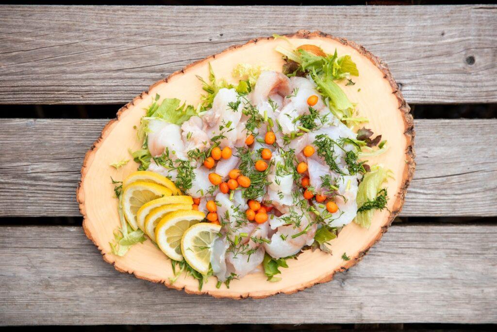 Herrankukkaron villiruokapöydän annos puukiekon päällä, annoksessa silliä, tyrniä ja sitruunaa.