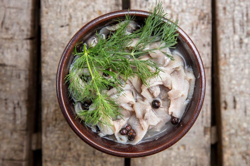 Lähikuva Herrankukkaron villiruokapöydän sillikulhosta, jossa marjoja ja tilliä.