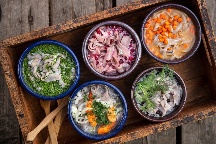 Herrankukkaron villiruokapöydän silliherkkuja astioissa ja eri mausteilla kuten marjoilla ja tillillä koristeltuna.