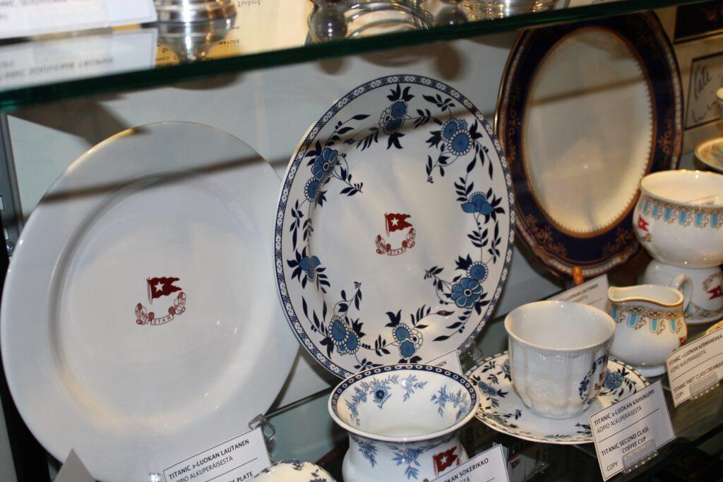Pienen Titanic näyttelyn vitriinissä White Star Linen kolme lautasta ja teekuppeja. Keskimmäinen lautaunen on sinivalkoisia ja kukkakoristeellisia.