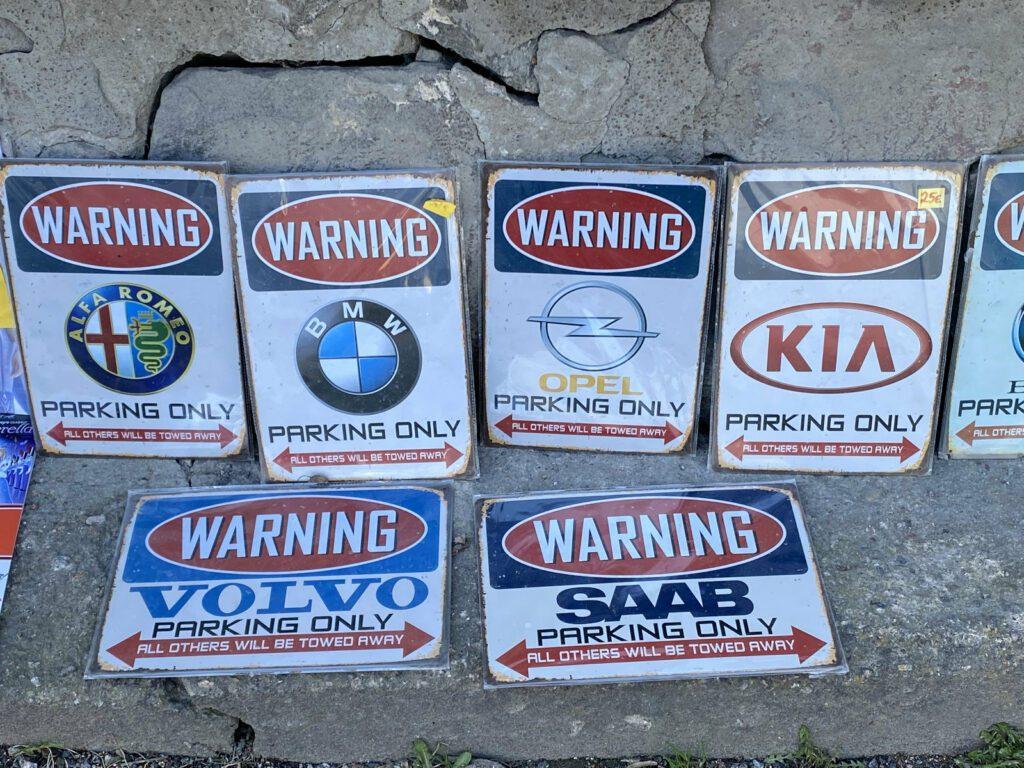 Kuusi matkamuisto-kylttiä, jossa automerkkien logoja ja teksti parking only.
