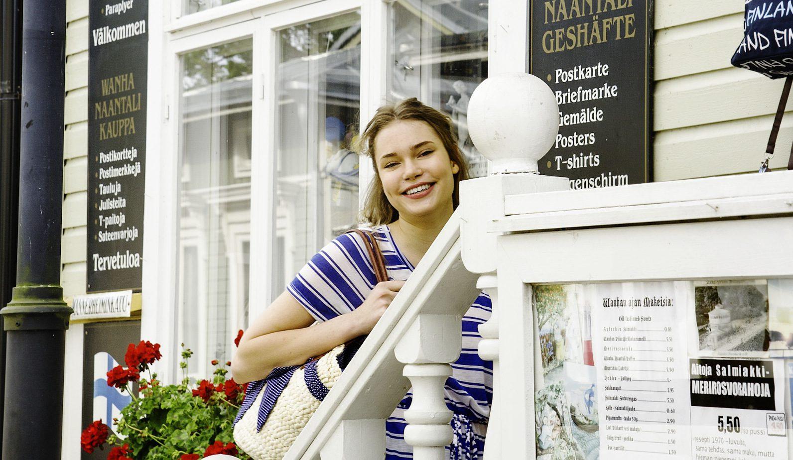Tyttö, jolla on sinivalkoraidallinenmekko, seisoo myymälän portailla, valkea kaide. Taustalla näyteikkuna ja mainostauluja.