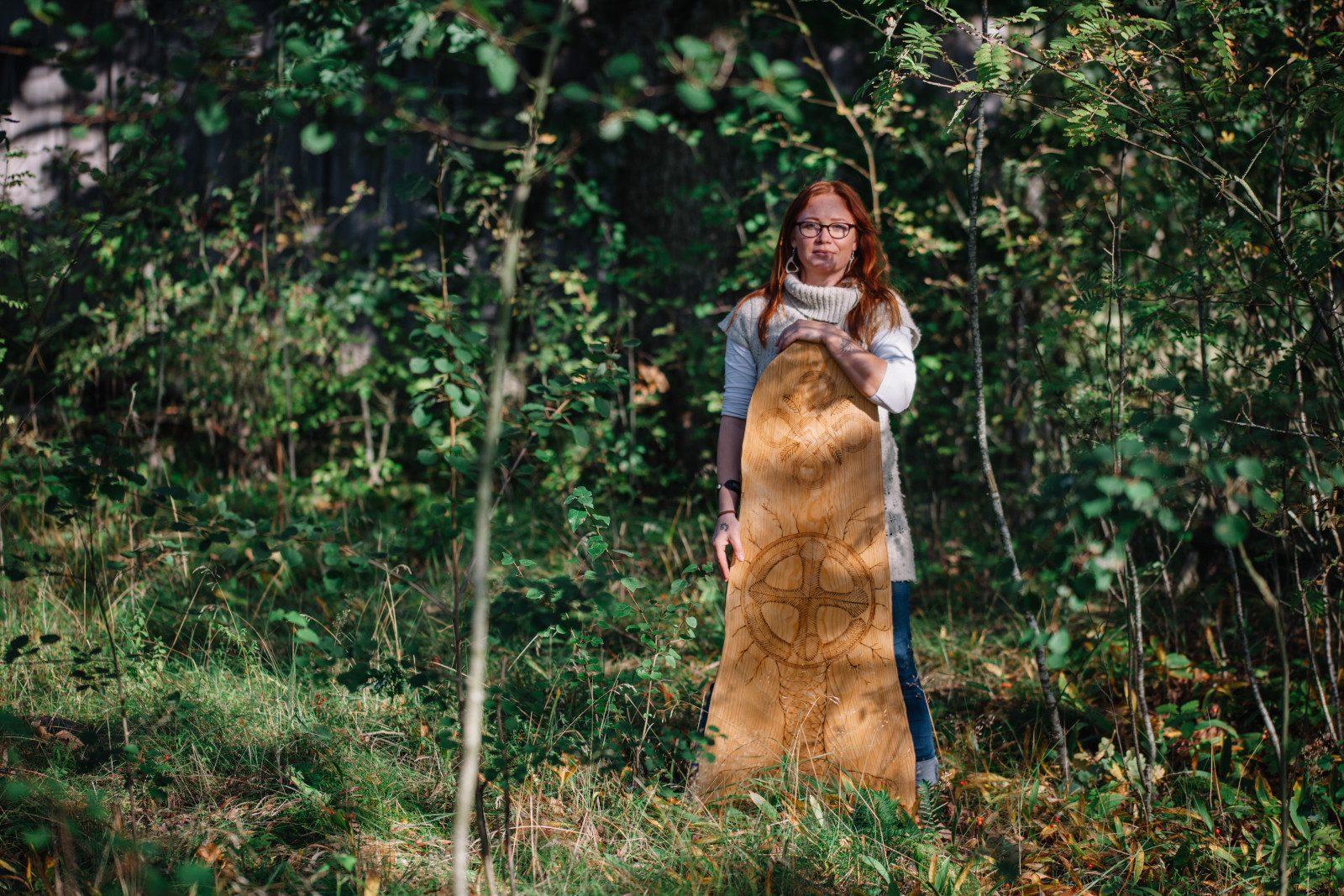 Kuppari-Hanna seisoo metsässä edessään hirsipuu, johon on polttokirjailtu taidetta.